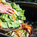 woman putting food scraps into a compost bin